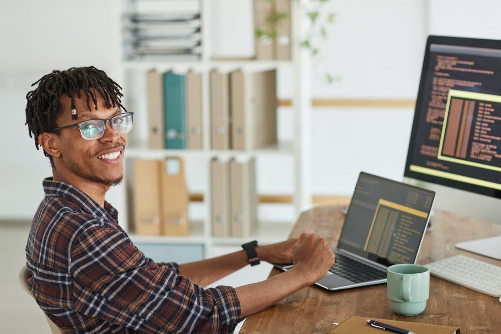 Smiling African-American Man Writing Programming Code