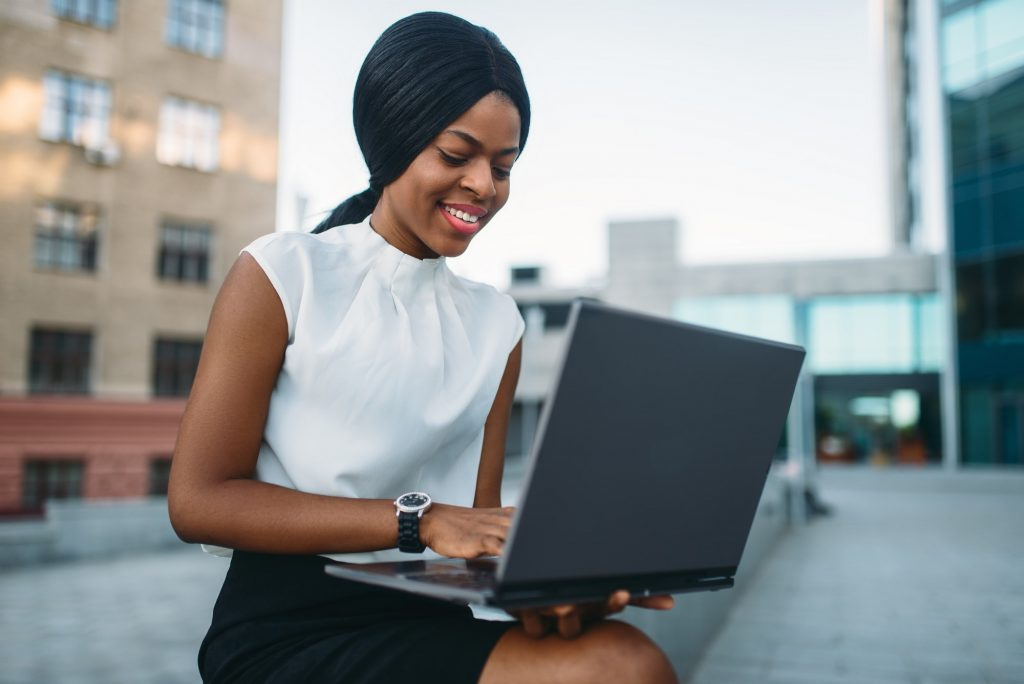 Business woman uses laptop against office building